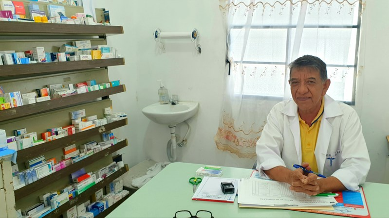 A Guatemalan pharmacist sits at his desk beside a cabinet of medicines