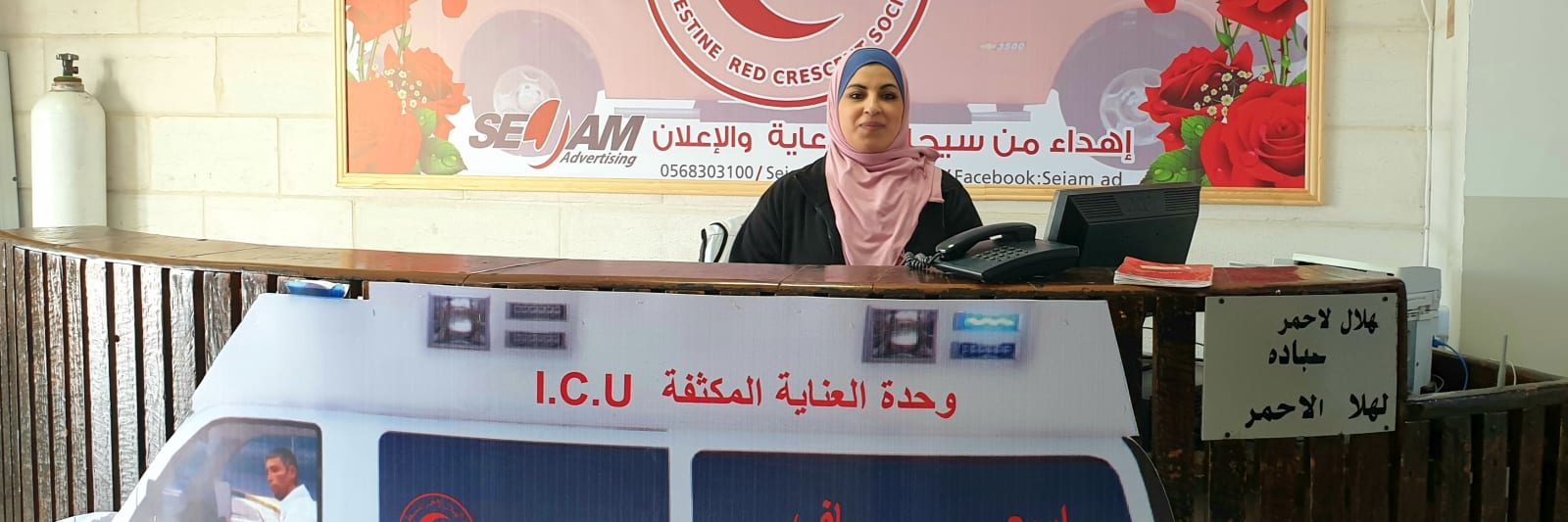 A woman smiles behind the reception desk of the Palestinian Red Crescent Society