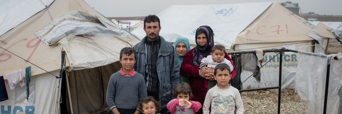 An Iraqi family stand together in a IDP camp
