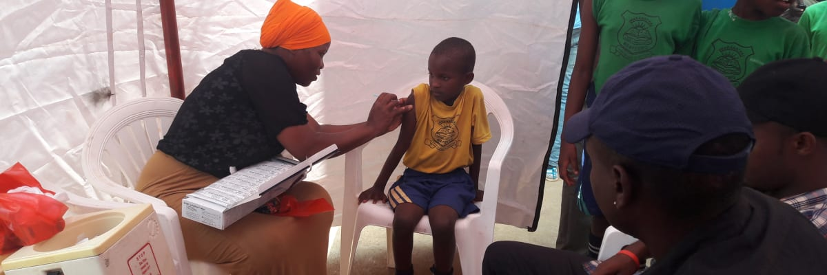 Nurse gives child an injection at a mobile clinic in Uganda