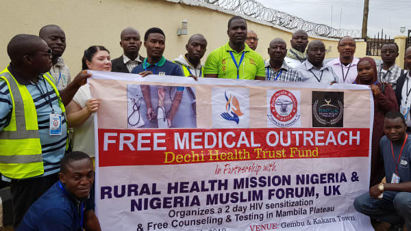 A group of medical staff show their clinic banner