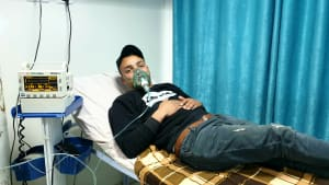 Khaled lies on a hospital bed with breathing apparatus over his nose and mouth